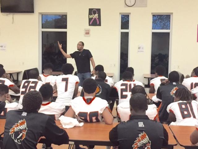 Erik Cummings speaks to football players at Miami Gardens High School.
