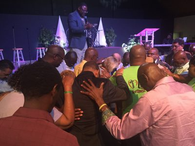 Jeffery Singletary, regional catalyst for the Central Region, leads participants of the Black/Multicultural Conference to pray for Dr. Tommy and Karen Green.